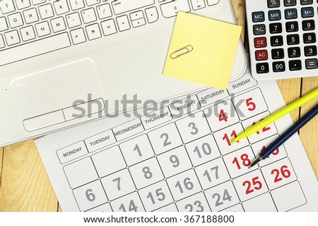 laptop with calendar and calculator on office desk