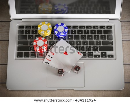 laptop with chips, dices and poker cards on the table