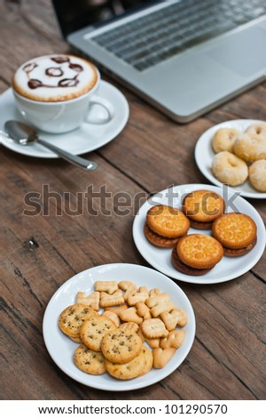 Laptop with coffee cup and snack on wood table - stock photo