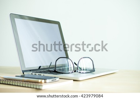 Laptop with eyeglasses in creative work place