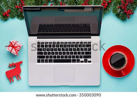 Laptop with gifts and coffee on table on cyan blue background. Business Holidays Concept. Office Workplace with Cup of Coffee and Christmas Decoration - stock photo