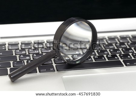 Laptop With Magnifying Glass.Close up - stock photo