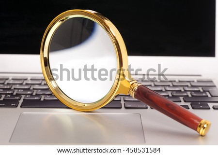 Laptop With Magnifying Glass close up - stock photo