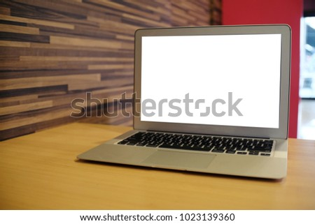 Laptop with Mock up blank screen on wooden table in front of coffeeshop cafe space for text. product display montage- technology concept.