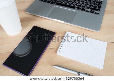 Laptop with paper cup, smartphone, pen and notepad with message on wooden desk. Morning workspace in office