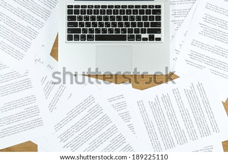 laptop with paper scattered - stock photo