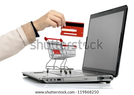 Laptop with small shopping cart and a hand with credit card isolated in white - stock photo