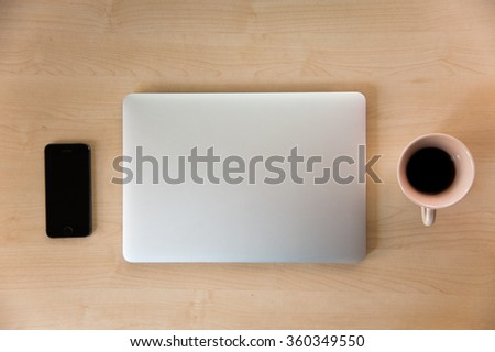 Laptop with smart phone and hot coffee on wood. View from above. - stock photo