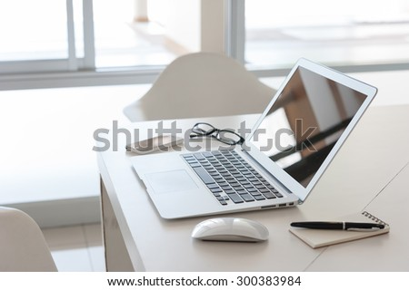 laptop with smart phone and note book on work desk - stock photo