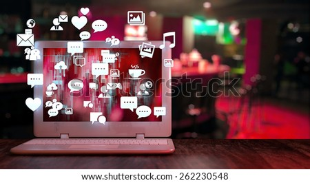 Laptop with social media related icons on a table and blurred pub background. Social media nightlife concept with space for text on the right side. - stock photo