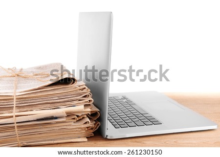 Laptop with stack of newspapers on table isolated on white - stock photo
