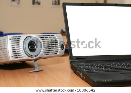 Laptop with the projector on office table - stock photo