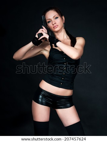 Lara Croft style woman with handgun on black background - stock photo
