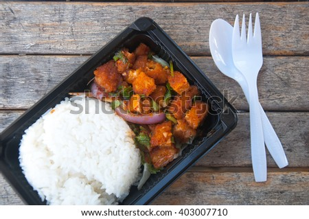 Larb with spicy salmon and rice in box lunch on the wooden table - stock photo