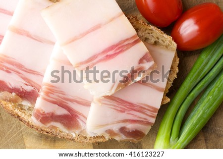 Lard on bread and other food. Wooden background