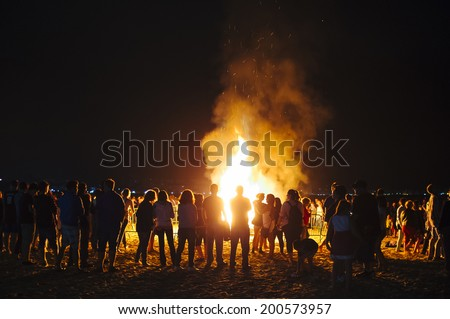LAREDO, SPAIN - JUNE 24, 2014: People celebrate St John's Eve around a bonfire in a beach in northern Spain. St John's eve celebration around a bonfire is reminiscent of Midsummer's pagan rituals.