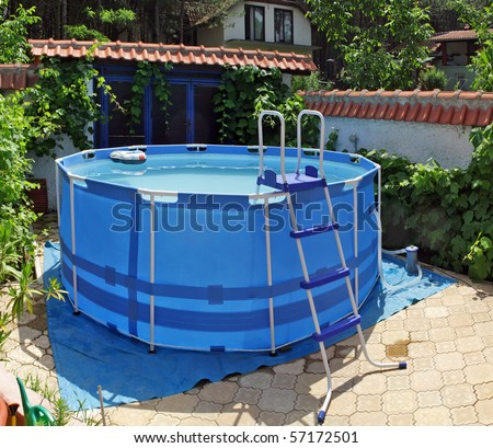 large above ground metal frame swimming pool in my back yard - stock photo