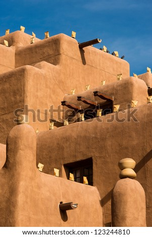 Large adobe building with luminaria on walls for the holidays - stock photo