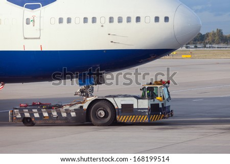 Large aircraft being pulled by airport tug tractor taxing on airfield into docking position for passenger boarding the airplane - stock photo