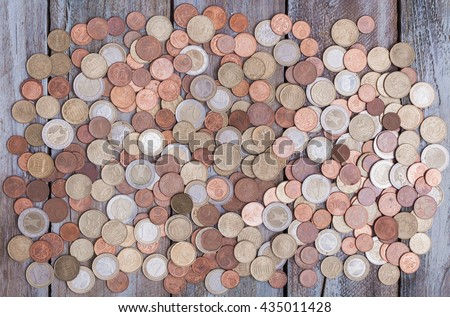 Large amount of Euro money coins on an aged grunge wood board desktop. - stock photo