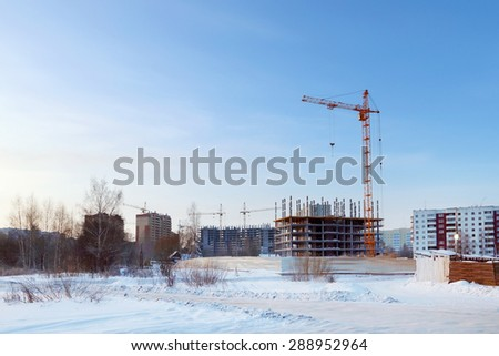 Large apartment buildings under construction in winter sunny day - stock photo