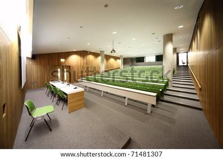 large auditorium with rows of green seats and white tables