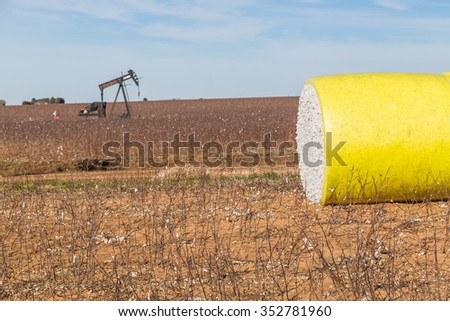 Large bale of cotton in bright yellow  protective wrap surrounded by harvested cotton field with pumping oil rig in background. - stock photo