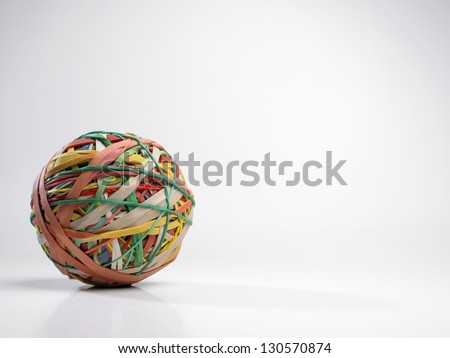 Large ball of rubber bands on a white background - stock photo