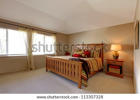 Large bedroom with wood bed and nightstand with stripe red, green and yellow bedding. - stock photo