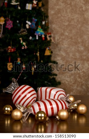 Large Blown Glass Peppermint Candy, Small Christmas Bulbs and snowflakes on a wooden table top in front of a Christmas tree. - stock photo
