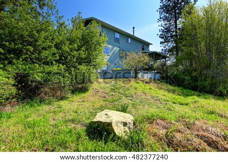 Large blue house exterior surrounded by trees and bushes. Northwest, USA