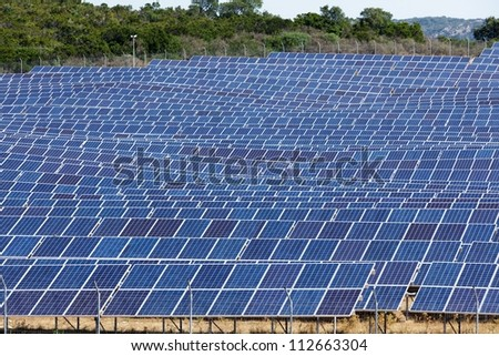 large blue solar panel field in sunny area - stock photo