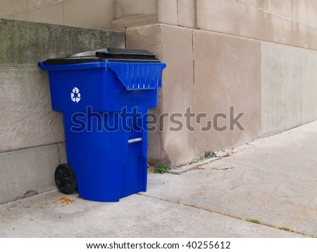 Large blue trash can with lid and wheels on an outdoor sidewalk in a city park. - stock photo
