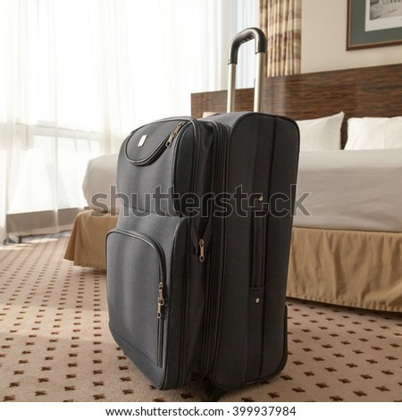 Large blue wheeled suitcase standing on the floor in the hotel room. Travel lifestyle concept. Square image - stock photo