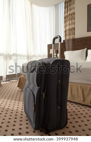 Large blue wheeled suitcase standing on the floor in the hotel room. Vertical image - stock photo