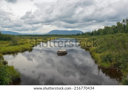 Large bog with calm waters reflecting storm clouds in the distance - stock photo
