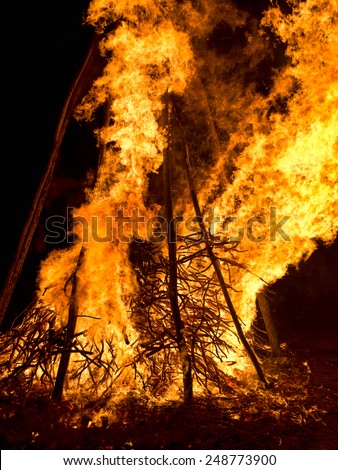 Large bonfire at night. Flames, sparks from celebratory fire - stock photo