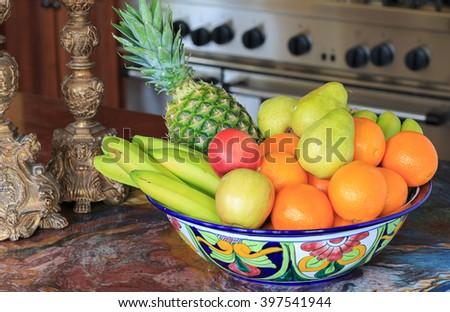large bowl of assorted fruit in elegant kitchen - stock photo