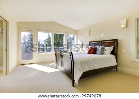 Large bright classic new bedroom interior with beige walls. - stock photo