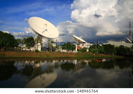 Large broadcast radars or satellite dishes with reflection on the pond - stock photo