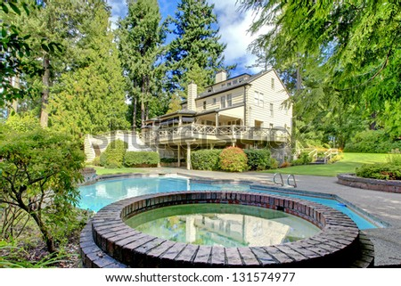 Large brown house exterior with summer garden with swimming pool. Northwest.