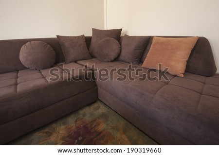 Large brown L-shaped sofa in a living room - stock photo