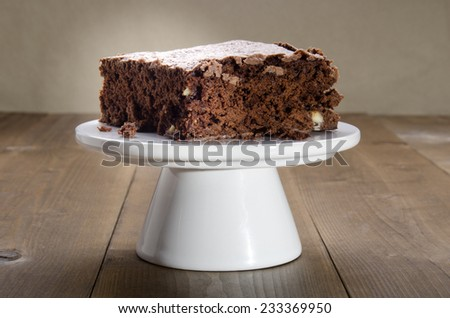 large brownie with white chocolate on a cake stand - stock photo