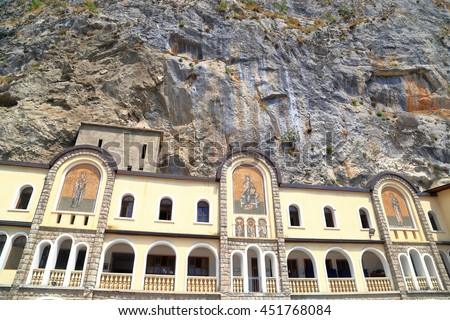 Large building of Ostrog Monastery under tall mountain cliffs, Montenegro