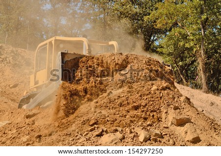 Large bulldozer moving rock and soil for fill for a new commercial development road construction project