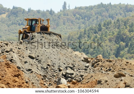 Large bulldozer moving rock in a hill removal for an airport runway expansion project in Oregon - stock photo