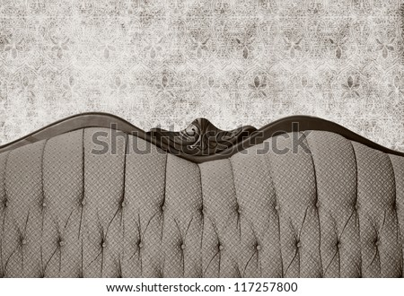 Large camel back antique couch with wallpaper background. Sepia toned.
