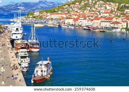 Large canal inside Venetian town of Trogir with boats anchored along pier, Croatia - stock photo