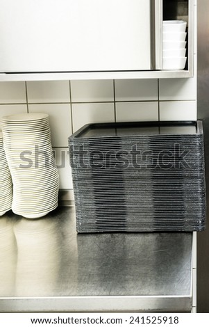 large canteen kitchen: opened cupboard with kitchenware inside, plates and trays - stock photo