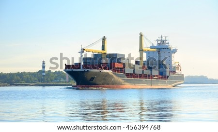Large cargo container ship leaving port in a bright sunny day. Riga, Latvia - stock photo